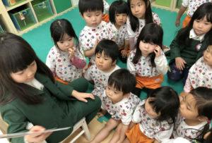 年長児が英語で本を読み、縦割り保育の中で自然と英語が身につきます